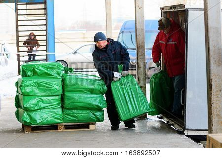 Moscow, Russia - December 13, 2016: Warehouse transport and logistics company. Worker puts on pallets loaded with green bags.