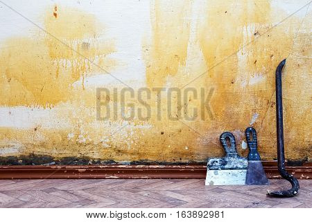 Construction background. Old wall spaces in which to make repairs. The wall, located the nail puller and spatulas.