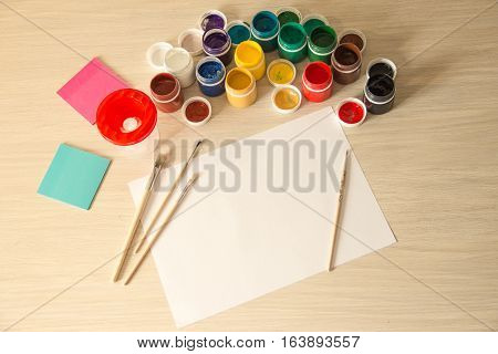 A white sheet of paper lies on a wooden table next to paints and brushes. Top down view.