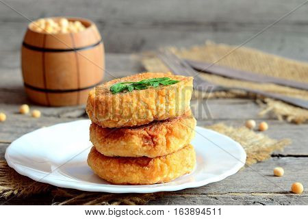 Fried vegetarian patties on a plate. Tasty patties made with boiled crushed peas, eggs, flour and spices. Vegetarian meal idea. Closeup. Cutlery on a wooden table