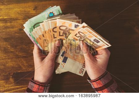 Female hands counting large amount of euro currency cash banknotes top view above office desk