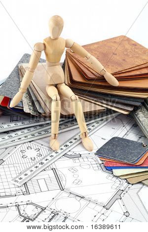 Wooden man, color samples of architectural materials - plastics,  Metric Folding ruler and architectural drawings of the modern house