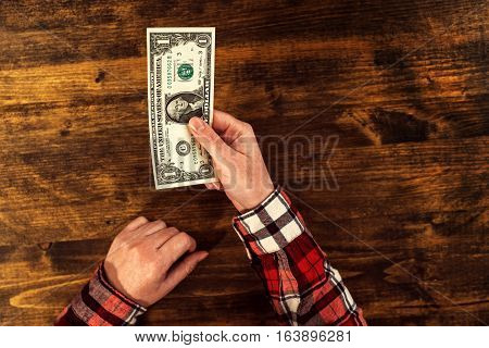Woman offering one dollar bill top view of business office desk