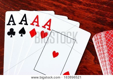 Four aces at a table. Poker concept.