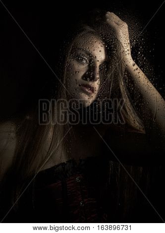 Portrait of a sensual young sexy woman wearing corset, touching her hair on black background.