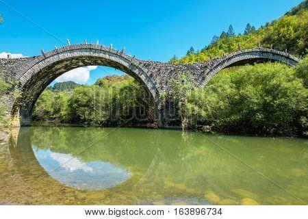 Three arches stone bridge of Kalogeriko (or Plakida) on the river of Voidomatis near the villages of Kipi and Koukouli in the Central Zagori. Greece