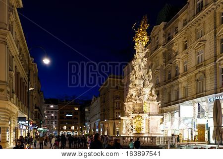VIENNA, AUSTRIA - MAY 17, 2016: Photo view on memorial plague column pestsaule and tourists on graben street at night with people