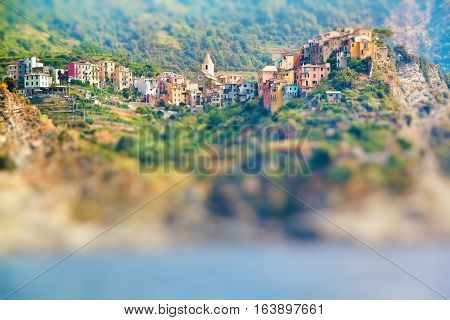Scenic view of colorful village Vernazza and ocean coast in Cinque Terre Italy. Miniature tilt shift lens effect.
