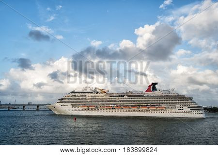 Miami USA - December 27 2015: Beautiful marine view with one large cruise liner ship of Carnival cruise line in port going to destination on cloudy blue sky backgroundat Miami Florida