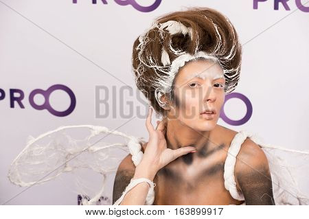 Kyiv Ukraine - September 16 2015: girl model with hair performs professional makeup and body art on masterclass at International exhibition of perfumery and cosmetics Intercharm as animal in white