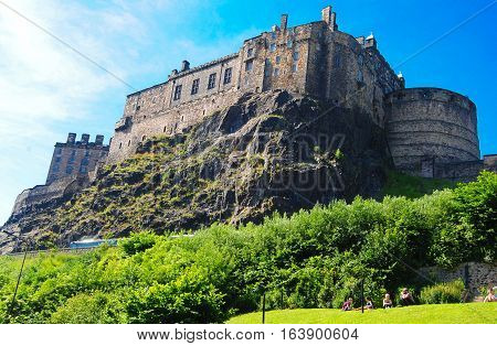 Edinburgh, United Kingdom - June 16, 2014. View of the Edinburgh castle sitting on the cliff, with vegetation and people.