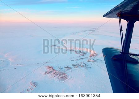 Flight of biplane above the snow covered endless tundra in time of short winter day.