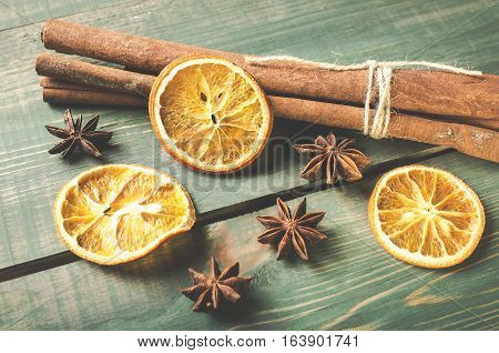 Dried orange anise and cinnamon sticks on green wooden table. Toned photo with selective focus.