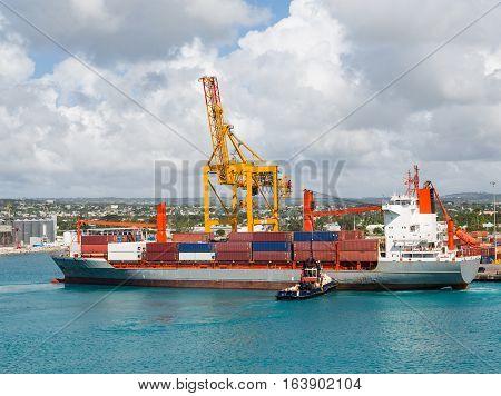 Freighter with Crane and Tugboat in Barbados