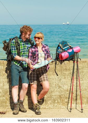Adventure summer tourism active lifestyle. Young couple backpacker looking at map by seaside plan their sightseeing
