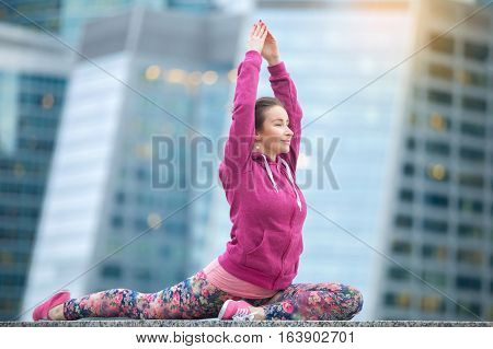 Young attractive woman practicing yoga, sitting in Single Pigeon, One Legged King Pigeon exercise, Eka Pada Raja Kapotasana pose, working out wearing sportswear, outdoor full length, city background
