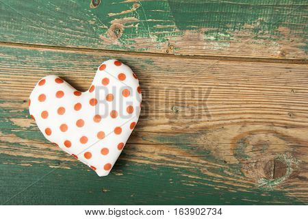 dotted heart on green wooden backgroung, copy space