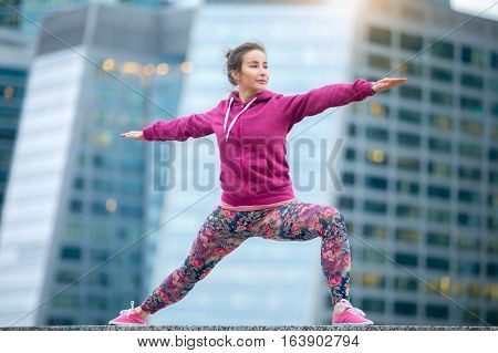 Young attractive woman practicing yoga, standing in Warrior two exercise, Virabhadrasana II pose, working out wearing pink sportswear, outdoor full length, modern skyscraper background