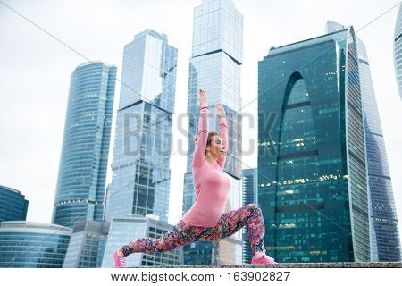 Young attractive woman practicing yoga, standing in Warrior one exercise, Virabhadrasana I pose, working out wearing pink sportswear, outdoor full length, modern skyscraper background