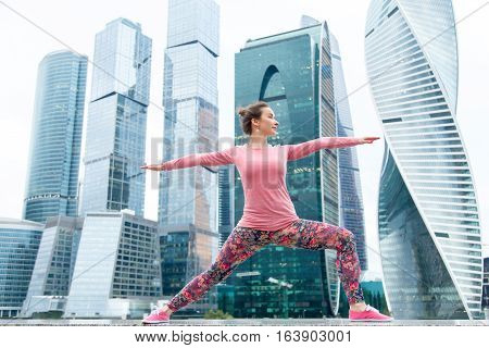Young attractive woman practicing yoga, standing in Warrior two exercise, Virabhadrasana II pose, working out wearing pink sportswear, outdoor full length, modern urban skyscraper background