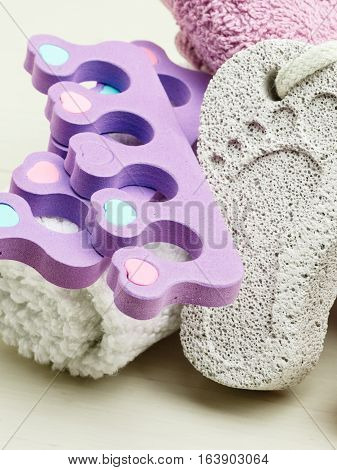 Foot care. Pedicure accessories set tools : pumice with footprint towel toe separators closeup