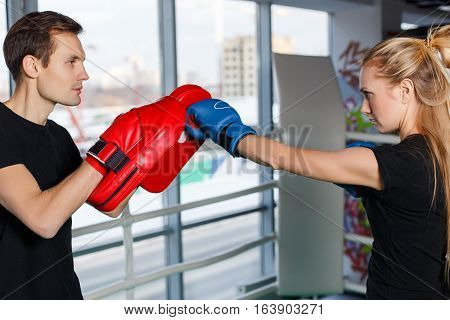 Coaching young athletes with trainer in boxing gloves in gym