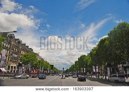 Paris, France - June 29, 2014. View of Champs-Elysees boulevard in Paris, with historic buildings, street traffic, people, trees and clouds in the sky.