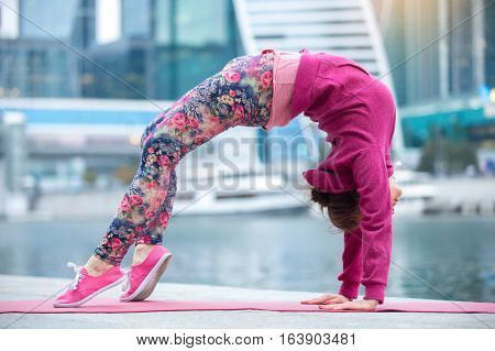 Young attractive woman practicing yoga, standing in Bridge exercise, Urdhva Dhanurasana pose, working out wearing pink sportswear, outdoor full length, modern urban city background