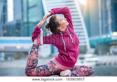 Young attractive woman practicing yoga, sitting in One Legged King Pigeon exercise, Eka Pada Rajakapotasana pose, working out wearing pink sportswear, outdoor full length, city and river background