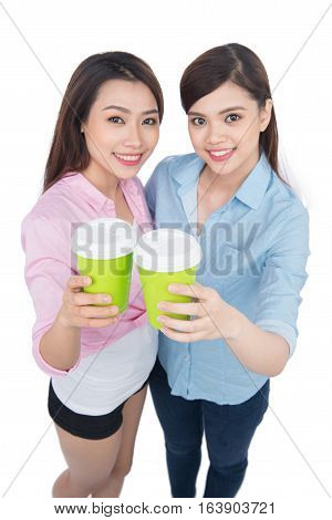 Two charming woman friends enjoying coffee on white background