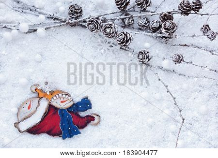 Larch Branches With Cones And Snowman On The Snow. Christmas Background With Space For Your Text.
