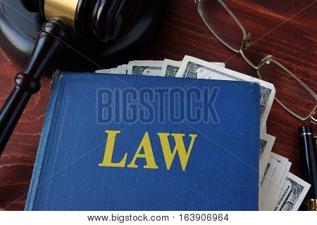 Book with Law, a gavel and cash. Corruption in a court concept.