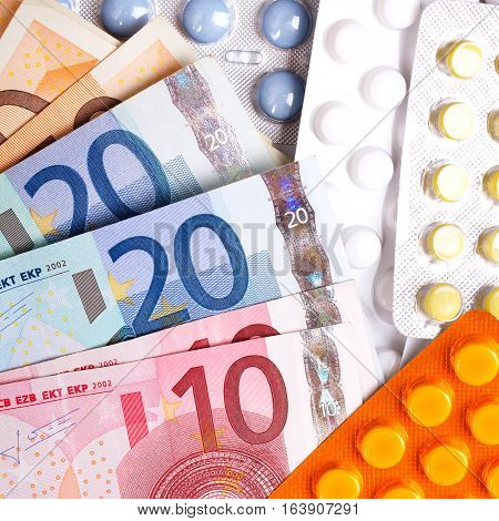 Euro money bills and colorful pills, tip view