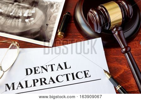 Dental Malpractice form, and gavel on a surface.
