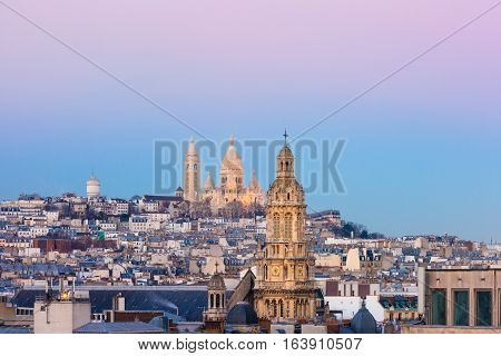 Aerial view of Sacre-Coeur Basilica or Basilica of the Sacred Heart of Jesus at the butte Montmartre and Saint Trinity church at sunset, Paris, France