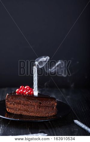 A slice of chocolate cake with redcurrant and a single extinguished candle on a dark background. Vertical shot
