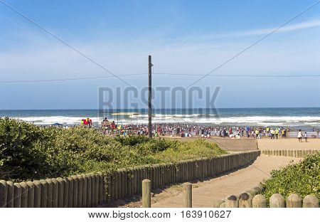 Green Dune Vegetation And People Against Blue Coastal Skyline