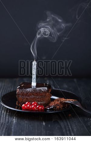 A slice of chocolate cake with redcurrant fork and a single extinguished candle on a dark background. Vertical shot