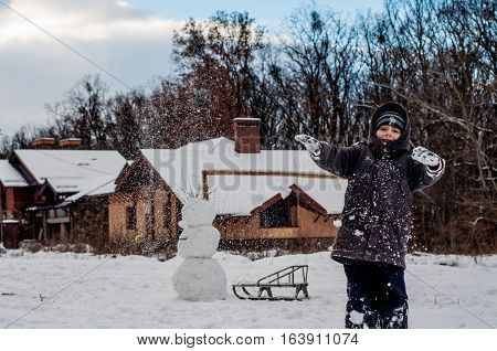 Boy throwing snowballs in the meadow near the house