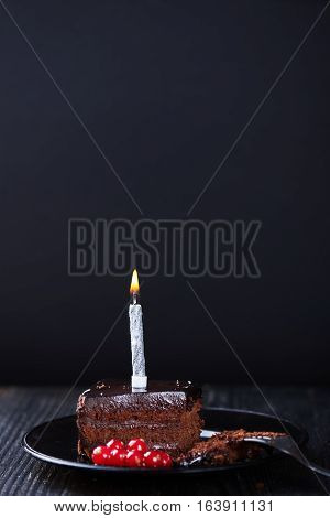 A slice of chocolate cake with redcurrant, fork and a single lit candle on a dark background. Dark photo. Vertical shot.