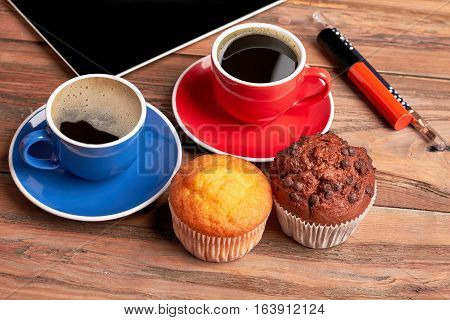 Muffins and cups of coffee. Lipstick and eyeliner on wood. Make a delicious brake.