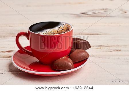 Cup of coffee and chocolates. Red dishware on wooden background. How to prepare coffee.