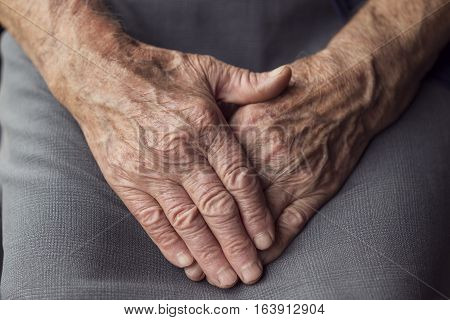 Detail of an elderly woman's wrinkled hands crossed and set in her lap. Selective focus