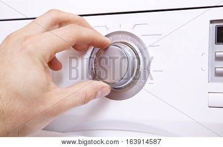 Man's hand sets the parameters of the control button.