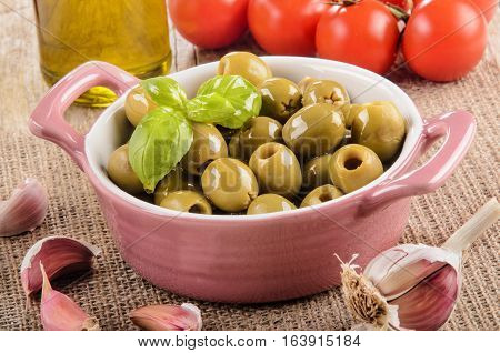 green olive in a pink bowl garlic tomatoes and olive oil in a glass bottle on jute
