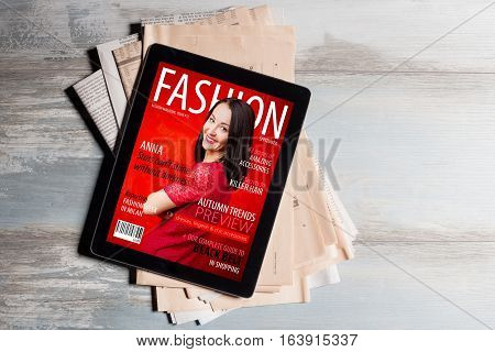 Fashion magazine cover on tablet computer on top of  newspapers