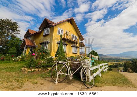 Vintage European style of yellow house in countryside of Mae Hong Son province near Chiang Mai Thailand with Blue sky and clouds.
