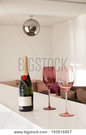 Bottle of champagne and two glasses in the luxurious interior of the penthouse