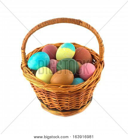 Colorful Easter eggs inside straw wicker brown basket isolate on white closeup