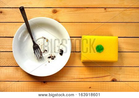 Dirty white plate in the white sink in the kitchen and yellow dish sponge with a drop of dish-washing detergent